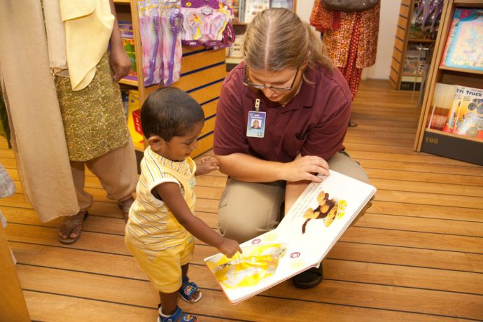 India: Kochi, India :: Emma Magnusson (Sweden) shows a book to a local child. More Info