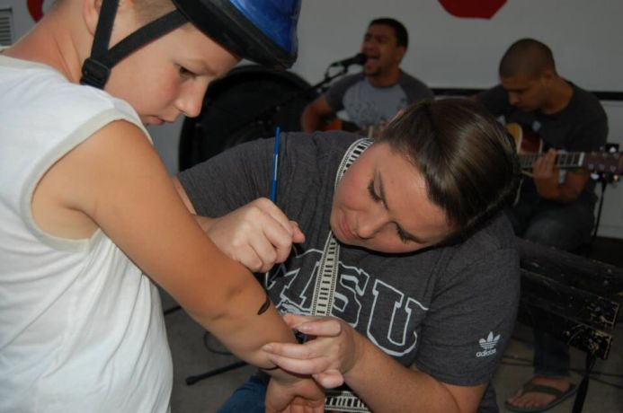 Bosnia & Hercegovina: Courtney (USA) paints a boys arm while team members play music in the background. The OM Bosnia team in Dobrinja has been encouraged by divine encounters recently. More Info