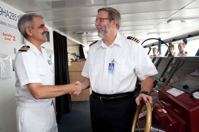 India: Visakhapatnam, India :: Left to right, Captain Pat Tracy (USA) shakes hands with Captain Tom Dyer (USA) on the bridge. More Info