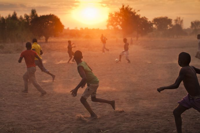 Africa: Children in the village of Mussa playing soccer barefoot at sunset. More Info