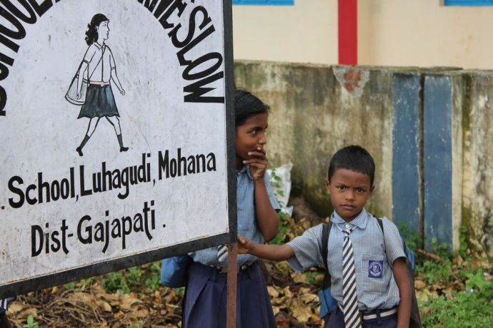India: A young boy leans on a sign near Luhagud school in Odisha, India. More Info