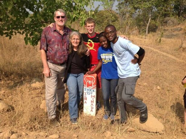 Angola: OM Angola team: Wessel, Joan and Tiago van der Merwe, Marta and Nando in front of mine warning sign  More Info