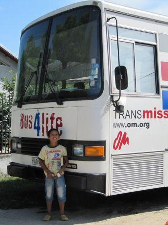 Romania: Child Posing in Front of Bus4Life after participating in the kids program  More Info