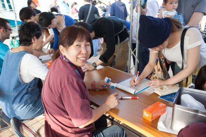 Japan: Kanazawa, Japan :: Local port volunteer Toyoko Banyama helps visitors register to come on board Logos Hope. More Info