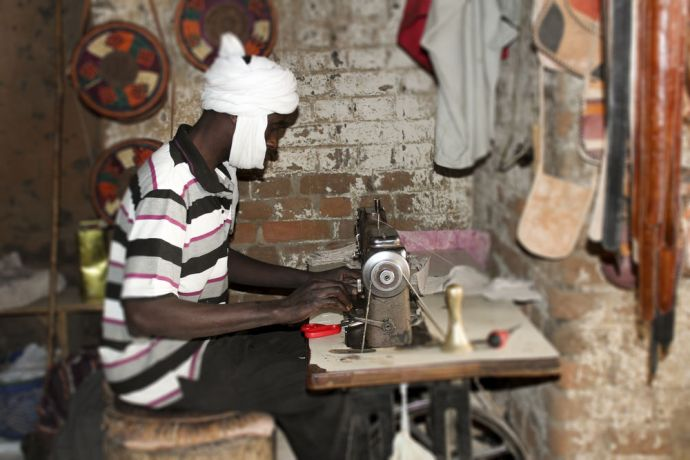 Africa: Chadian man in his sewing business. He makes leather products like bags and shoes. More Info