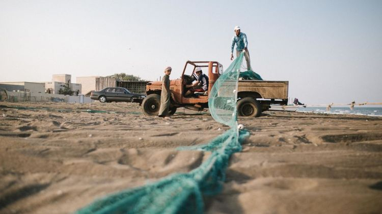 Arabian Peninsula: Fishermen pull in their nets at the end of the day in this fishing village.