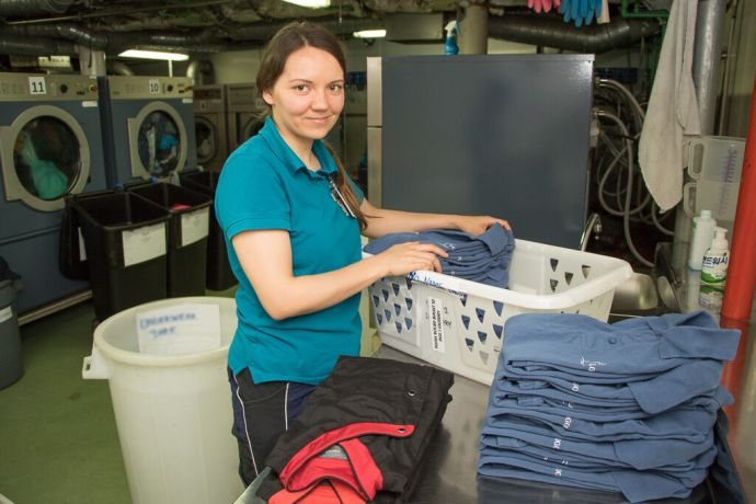 Singapore: At Sea :: Tanya Rychkova (Russia) folds work uniforms in the laundry room as part of the Hotel Services Department. More Info