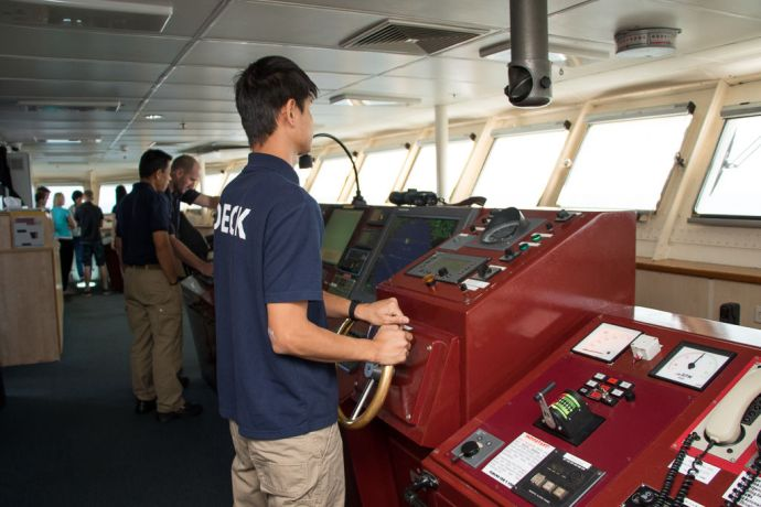 Singapore: At Sea :: Deck Rating, Eddy Lee (Taiwan) steers Logos Hope from the bridge as she sails from Singapore to Malaysia. More Info