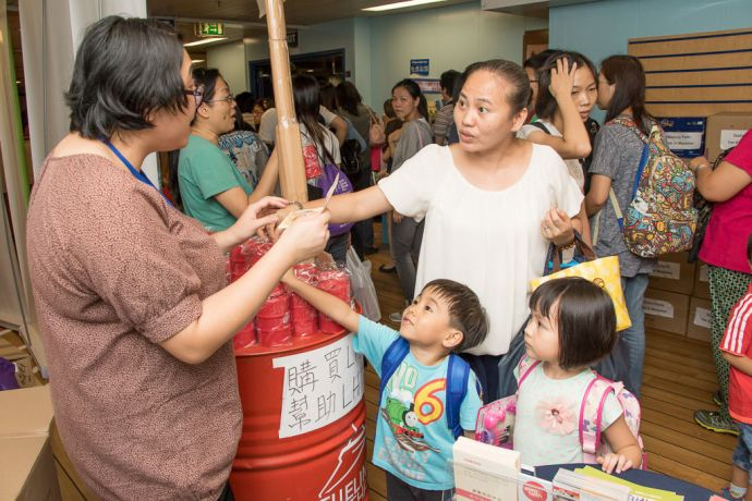 Hong Kong: Hong Kong, Hong Kong :: A family buy a fuel can money bank to help raise money for the Fuel for Hope Fund onboard in the hope experience deck. More Info