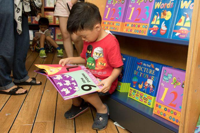 Hong Kong: Hong Kong, Hong Kong :: A boy enjoys reading book in the bookfair. More Info