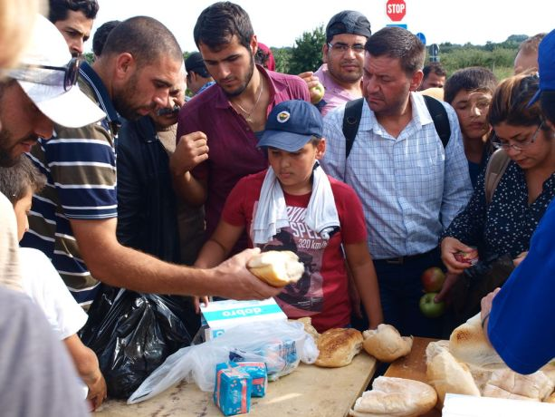 Serbia: Refugees at a Hungarian border crossing in Serbia queue for bread brought by Christian volunteers.  More Info