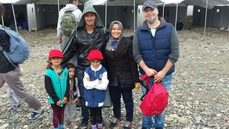 Macedonia: A refugee family in a camp in Macedonia receive some essential clothing. More Info