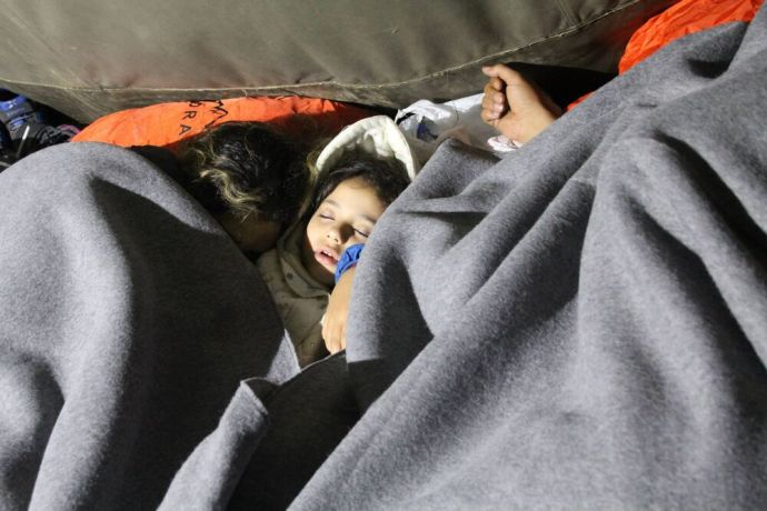 Montenegro: At a Serbian border crossing, exhausted refugee families sleep huddled together under blankets. More Info