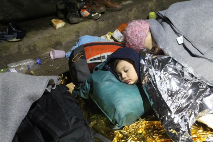 Serbia: At a Serbian border crossing, a refugee child sleeps under a space blanket for warmth, using a bag as a pillow. More Info