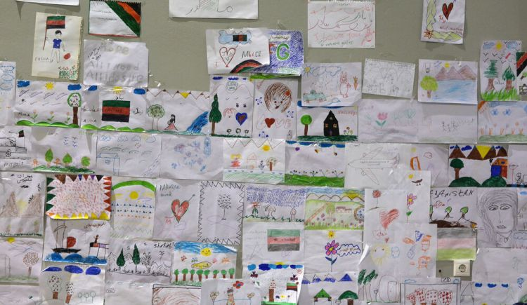 Greece: Childrens drawings at Galatsi camp transitioning from pencilled drawings into rainbow-coloured sketches of houses, flags, mountains, trees. One papers message recorded a childs single wish: Hope. All I need.  All I desire. More Info