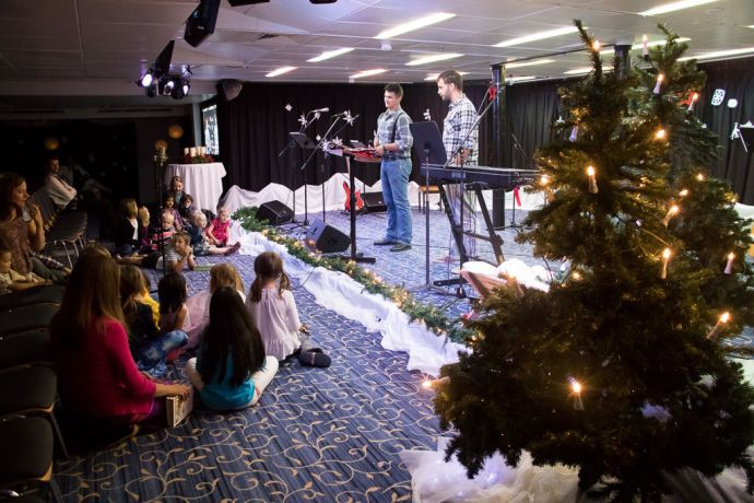 Mauritius: At Sea :: Rainier Penner (Canada) and Henrik Scharton (Germany) are the emcees at the European/North America Advent Sunday Service in the Logos Lounge and pray for the children onboard before Sunday School. More Info