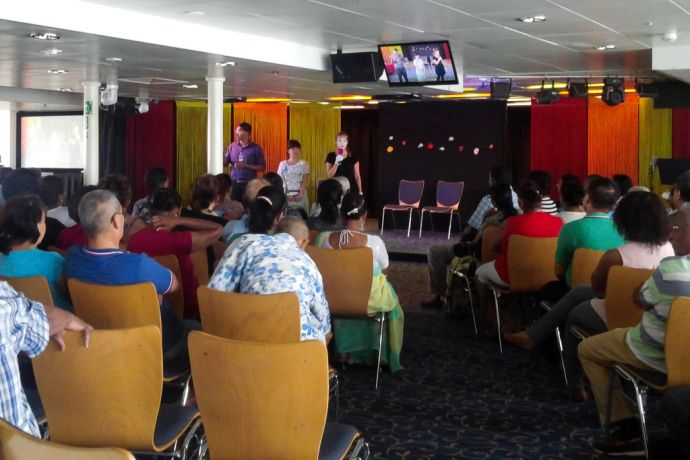 Mauritius: Port Louis, Mauritius :: Leonie Blum (Germany) explains a mime after the performance at an onboard event to encourage senior citizens in the Logos Lounge. More Info
