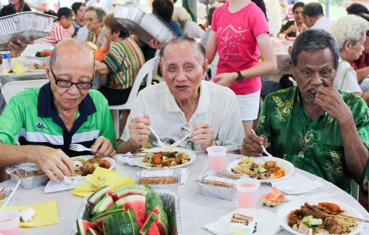 Singapore: Elderly and needy residents enjoy a sponsored meal at a Christmas party. More Info