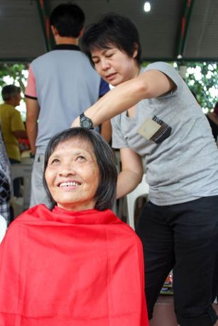 Singapore: An OM volunteer cuts hair for an elderly resident at a Christmas party. More Info