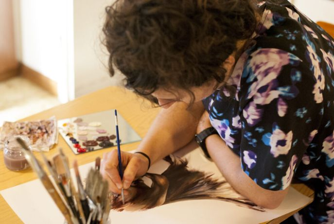 Italy: During OM Arts Incarnate, Emily Woolerton paints portraits inspired by colors of personalities.   Photo by Lauren OShea More Info