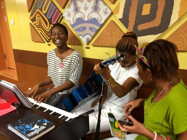 Tanzania: Dar es Salaam, Tanzania :: Vision Team member Mainala Silondwa (Zambia) spends time with two locals singing and playing the piano in the International Café on board Logos Hope. More Info
