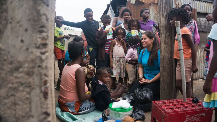 Mozambique: Maputo, Mozambique :: Crewmember Gabi Camargo (Brazil) prays for a homeless woman and her child who sells what little they have in a village in Maputo. More Info