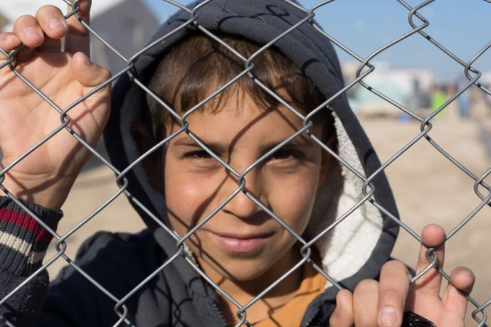 Australia: A child looks through the chain link fence of a large camp for Internally Displaced Persons (IDPs) in northern Iraq.  Photo by Andrew W. More Info