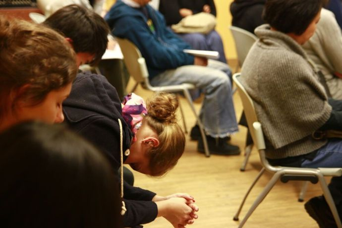 Hong Kong: A young woman participates in a prayer meeting with ministry team. More Info