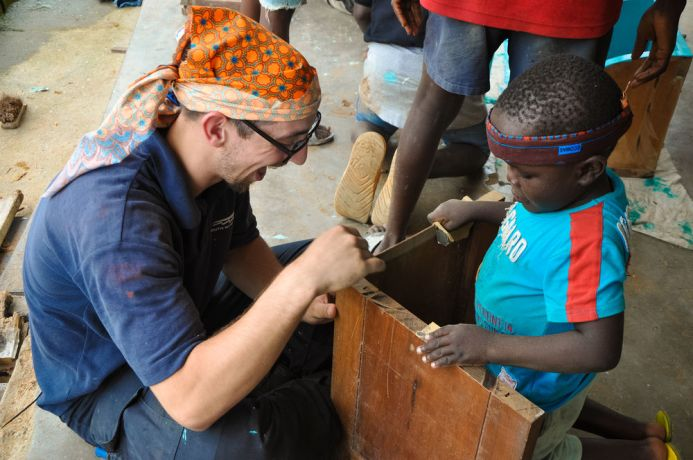 Cameroon: Douala, Cameroon :: A Cameroonian boy helps crewmember Job Ephraim (Netherlands) build cupboard shelves for a home for street kids. More Info