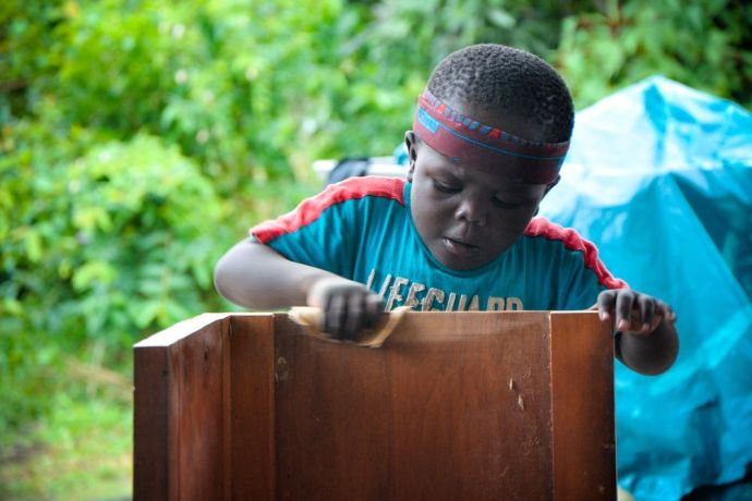 Cameroon: Douala, Cameroon :: Bobo, a Cameroonian boy, follows the example of Logos Hope crewmembers as they refurbish his home for street kids. More Info