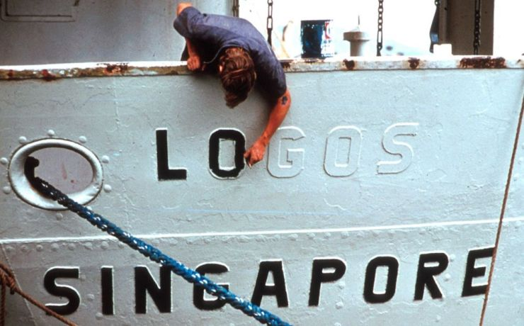 Ships: Painting the name Logos on the first OM ship after her purchase. More Info