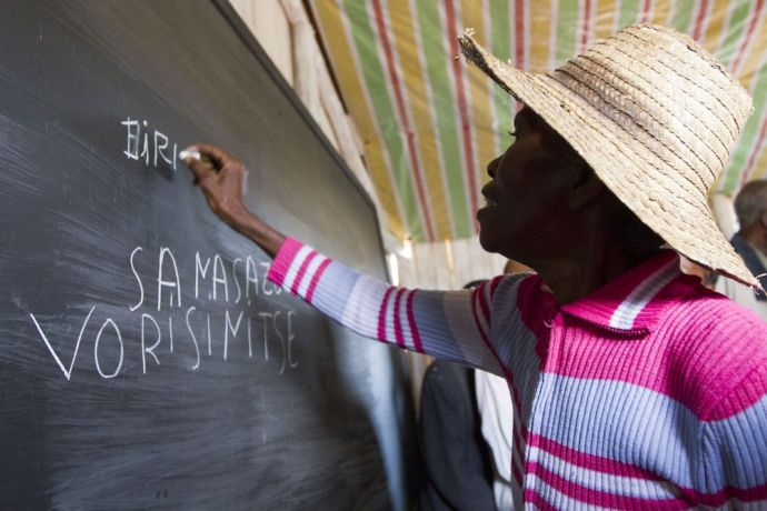 Madagascar: A woman proudly writes her name on the blackboard at a school opening. The one-roomed school was built by the community itself. OM has been building a relationship with the village over the past few months through fellowship and trainings. One of those trainings was Literacy training which two of the local ladies took up and started under a tree with 20 students of all ages. More Info