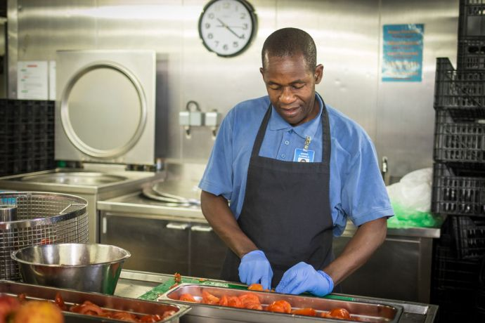 Cape Verde: At Sea :: Dennis Kamwela (Zambia) prepares lunch for Logos Hopes crewmembers. More Info