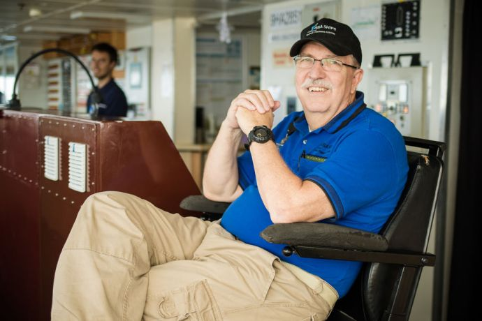 Ships: At Sea :: Logos Hope Captain Tom Dyer (USA) sits in the captains chair on the bridge. More Info