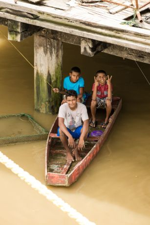 Guyana: Georgetown, Guyana :: Boys sit in a boat under a pier watching the arrival of Logos Hope. More Info