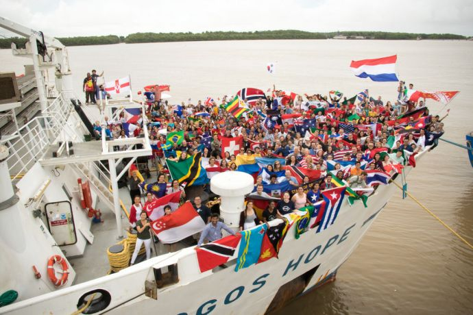 Guyana: Georgetown, Guyana :: Logos Hope crewmembers wave their country flags on the bow. More Info