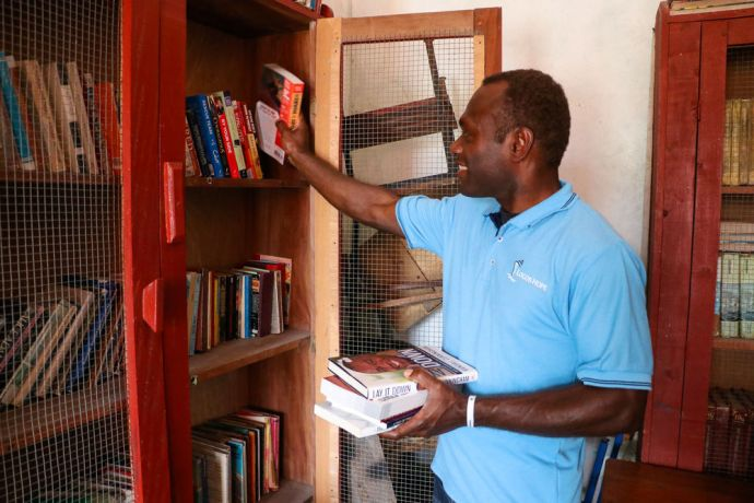 Guyana: Georgetown, Guyana :: Collin Kepas (PNG) places books donated by Logos Hope on the shelves of Timehri Prisons library. More Info
