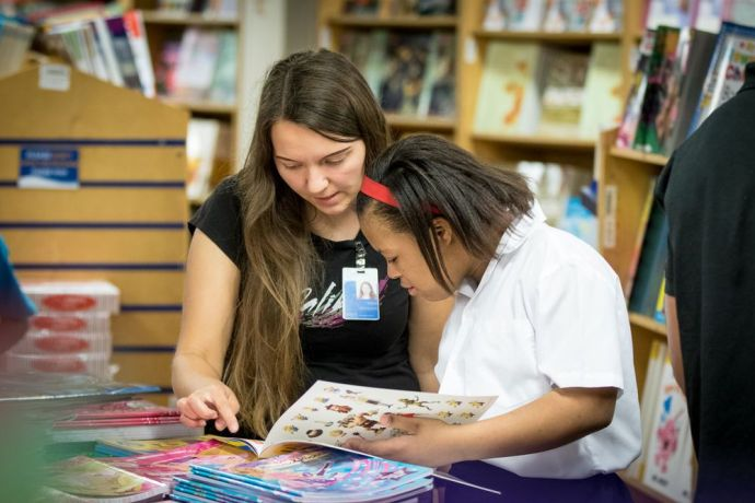 Trinidad & Tobago: Port of Spain, Trinidad  Tobago :: Tanya Rychkova (Russia) reads with a girl during a special book fair opening, exclusively for autistic children and their carers. More Info