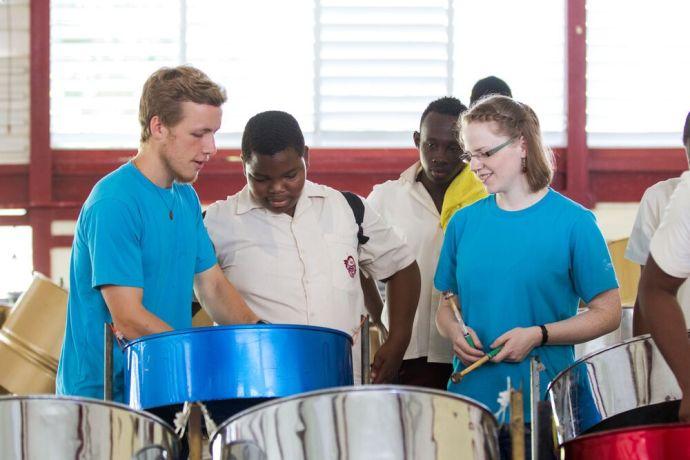 Trinidad & Tobago: Port of Spain, Trinidad  Tobago :: Boys of East Mucurapo Secondary School teach Nathanael Scott-Perry (UK) and Antonia Kinas (Germany) to play the steel pan, Trinidad and Tobagos national instrument. More Info