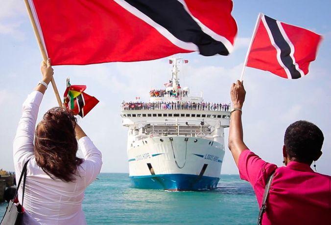 Trinidad & Tobago: Scarborough, Trinidad  Tobago :: Two Tobagoians wave their flags as Logos Hope arrives into Scarborough, Tobago. More Info