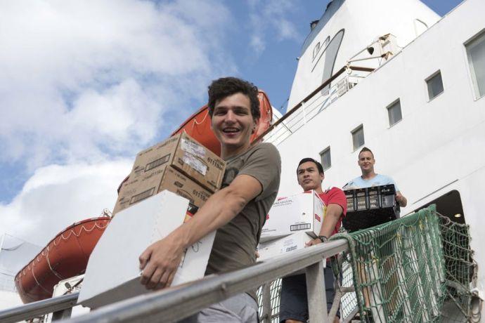 Curaçao: Willemstad, Curacao :: Crewmembers (l-r) Micha Roggensinger (Switzerland), Boyd Srisakunphaet (Thailand) and Hugo van Nigtevecht (Netherlands) leave Logos Hope ahead of dry dock. More Info