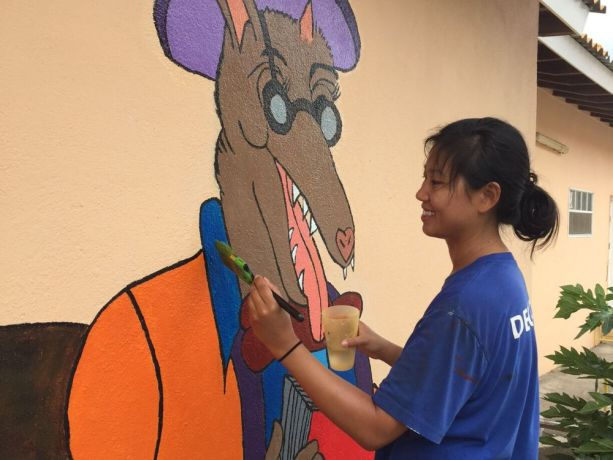 Curaçao: Willemstad, Curaçao :: Kathy Mew (USA) painting a character on the wall of an after school reading club. More Info