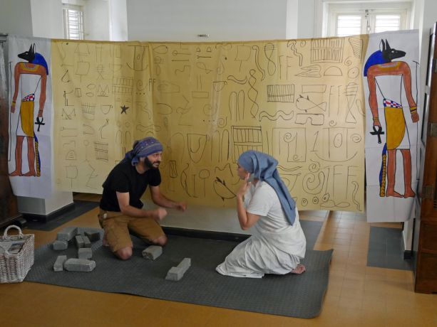 Curaçao: Willemstad, Curaçao :: Greg and Anne Pelletey (France) perform as Israelites forced to make bricks in a play for children at an after-school club. More Info