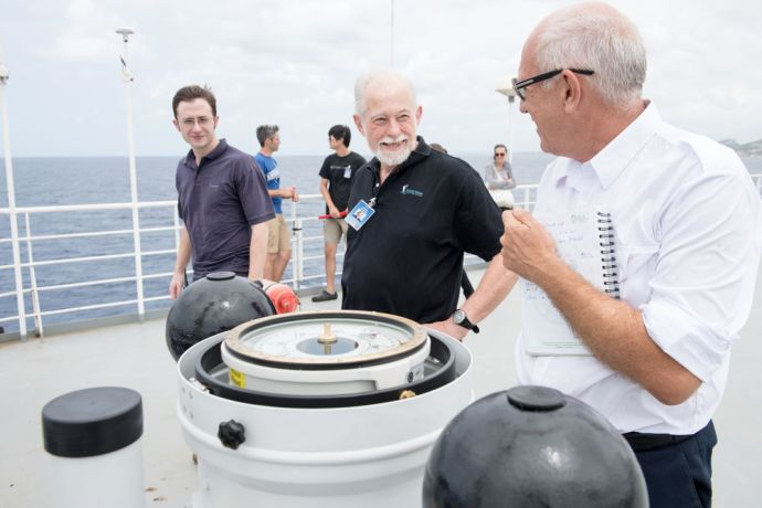 Curaçao: Willemstad, Curacao :: Captain Chris Hughes (UK), James Berry (UK) and compass adjuster Cornelis J van Santen talk as they adjust the new magnetic compass on deck nine. More Info