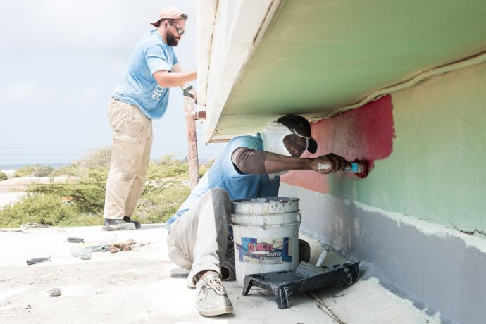 Aruba: Oranjestad, Aruba :: Alex Osiadacz (USA) works alongside Pastor Edsel Granviel to brighten up El Camino church with a fresh coat of paint. More Info