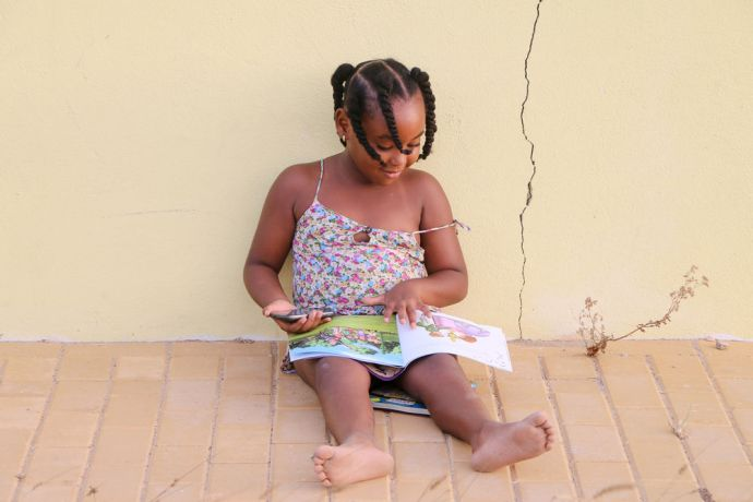 Aruba: Oranjestad, Aruba :: A young Aruban girl sits on the side of the road reading the new books she received from a team of Logos Hope volunteers who came to her neighbourhood. More Info