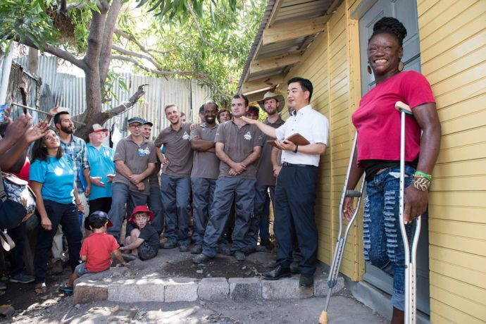 Jamaica: Kingston, Jamaica :: Keisha Syblis stands in front of her new house as Logos Hope Director Pil-Hun Park (South Korea) and the ship's maintenance team dedicate the home and hand over the keys. More Info