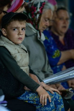 Ukraine: A young boy listens cautiously during a church service in eastern Ukraine as mortars go off in the distance. - Photo by Garrett N More Info