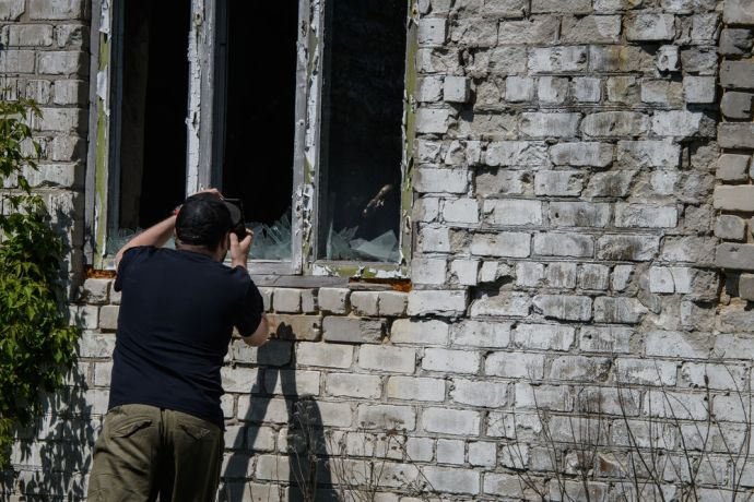 Ukraine: A Ukrainian man take a picture with his phone of the destruction caused by war within the conflict zone of eastern Ukraine.  Photo by Garrett N More Info