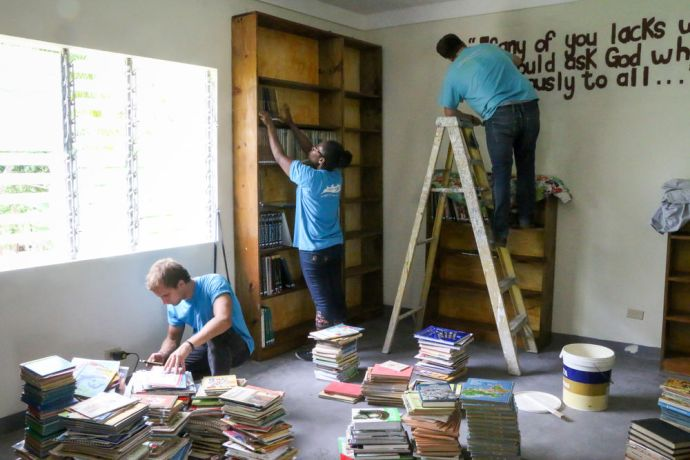 Jamaica: Montego Bay, Jamaica :: Ruven Klunk (Germany) and Daniella Laxabul (Papua New Guinea) organise books as Tom Chittock (UK) paints a Bible verse on the wall of a library for deaf people. More Info